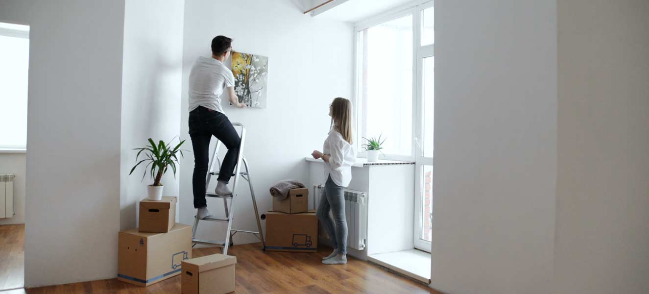 Couple hanging artwork on the wall.
